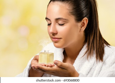 Close up portrait of woman in white spa gown smelling essential oil fragrance.Girl holding little bottle with aromatic scent.