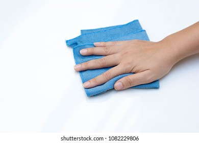 Close up portrait of woman's hand cleaning her white car