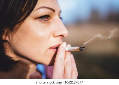 Close up portrait of women smoking outdoors