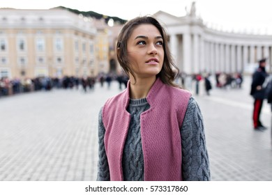 Close up portrait of wonderful woman in the city. She has a bright dark hair and charming smile. Background the city.