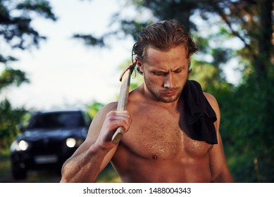 Close up portrait of woodsman with axe in hand. Handsome shirtless man with muscular body type is in the forest at daytime.