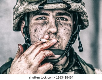 Close up portrait of wounded soldier, U.S. marine with dirty face, holding cigarette with soiled in blood fingers and smoking. Military medic resting after field operation. Traumatic war experiences