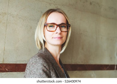Close up portrait of young 35 year old woman wearing brown eyeglasses and jacket