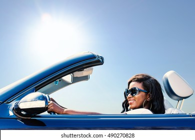 Close up portrait of young african girl taking blue convertible for a test drive.