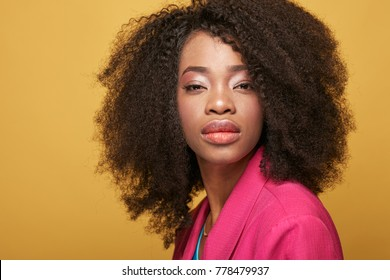 Close up portrait of young african girl with afro hairstyle. Girl wearing pink jacket, posing on yellow background. Studio shot