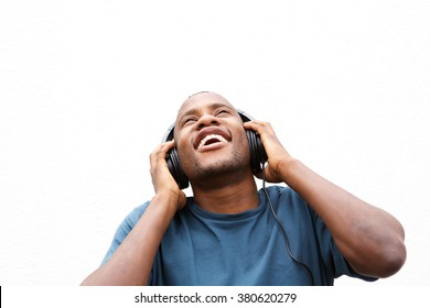 Close up portrait of young african guy enjoying music on headphones against white background
