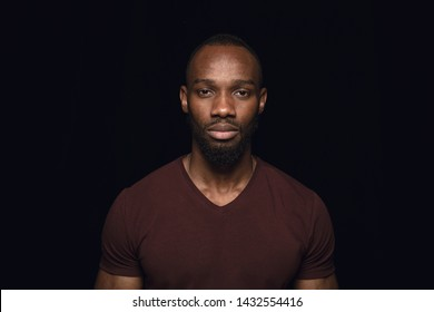 Close up portrait of young african man isolated on black studio background. Photoshot of real emotions of male model. Standing and looks serious. Facial expression, human nature and emotions concept.