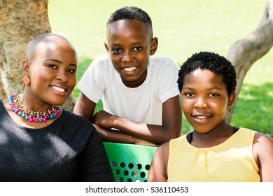 Close up portrait of young african mother with two kids in outdoor park.