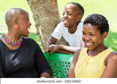 Close up portrait of young African mother spending quality time with kids in outdoor park.