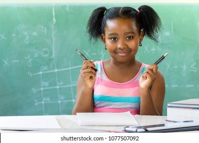 Close up portrait of young african student holding pen and pencil at desk in classroom with black board in background.