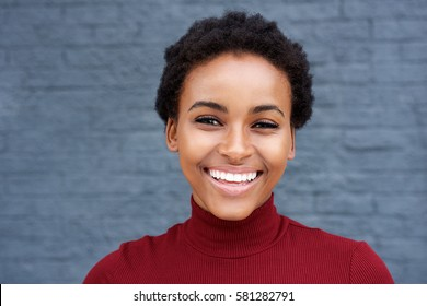 Close up portrait of young african woman smiling against gray wall