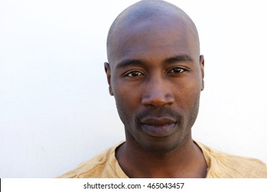 Close up portrait of young afro american guy against white wall