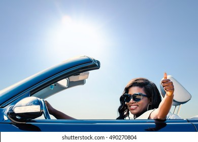 Close up portrait of young afro american girl sitting in convertible doing thumbs up.
