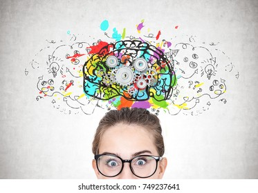 Close up portrait of a young astonished woman wearing round glasses and standing with an open mouth near a concrete wall with a large and colorful brain sketch with gears on it