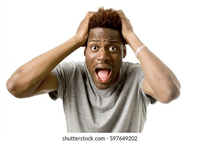 close up portrait of young attractive afro american man desperate in shock  with opened mouth and wide open eyes in disbelief and worried face expression isolated on white background