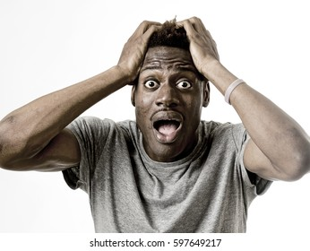 close up portrait of young attractive afro american man desperate in shock  with opened mouth and wide open eyes in disbelief and scared face expression isolated on white background