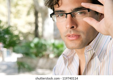 Close up portrait of a young and attractive businessman looking at the camera while holding his reading glasses with his hand.