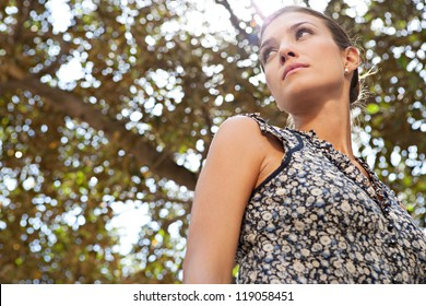 Close up portrait of a young  attractive businesswoman against a tree and the sun.