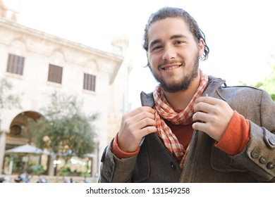 Close up portrait of a young attractive fashionable man grooming himself with a winter jacket and a scarf during a sunny day, smiling.