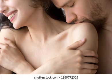 Close up portrait young attractive happy couple in love in bed. Male gently with tender kisses shoulder of beloved happy smiling female. Passionate romantic relations and having sex concept