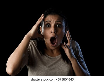 close up portrait young attractive Latin woman desperate and scared isolated on black background looking terrorized and horrified screaming in primal fear emotion face expression