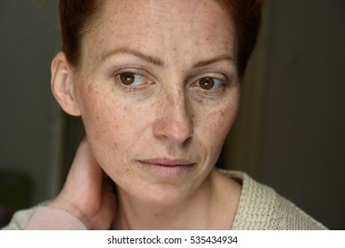 Close up portrait of young attractive red hair woman without makeup thinking about problems feeling pain in the neck and holding hand on it looking away