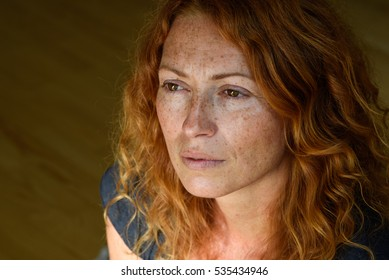 Close up portrait of young attractive red hair woman without makeup thinking about problems feeling depressive  looking away