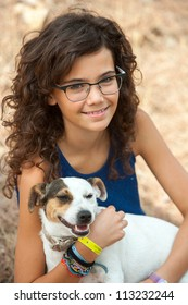 Close up portrait of young attractive teenage girl with her dog outdoors.