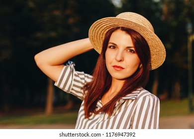 close up portrait of young attractive woman wearing striped dress and straw hat