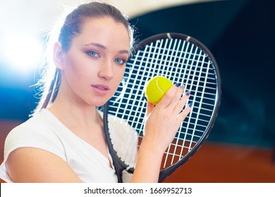 Close up portrait of a young attractive woman tennis player holding tennis racket