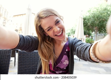 Close up portrait of a young attractive woman holding a smartphone digital camera with her hands and taking a selfie self portrait of herself winking at he camera. Travel and technology outdoors.