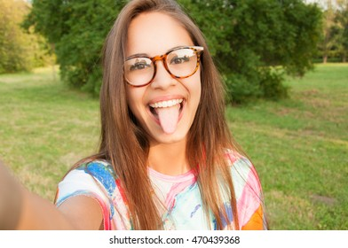 Close up portrait of a young attractive woman holding a smartphone and taking a selfie
