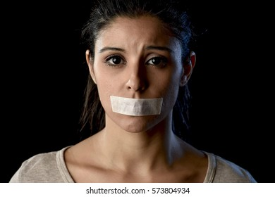 close up portrait of young attractive woman with mouth and lips sealed in adhesive tape restrained and abused censored and banned to speak and express opinion in freedom concept