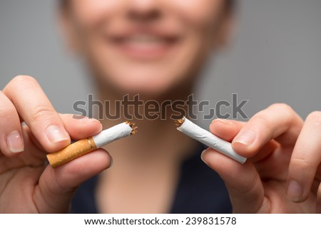 Close up portrait of young attractive woman breaking down cigarette to pieces. Studio shot selective focus isolated on grey. Addiction concept