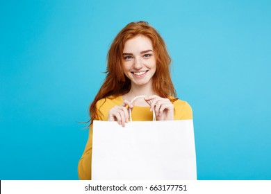 Close up Portrait young beautiful attractive redhair girl smiling with white shopping bag. Blue Pastel Background. Copy Space.