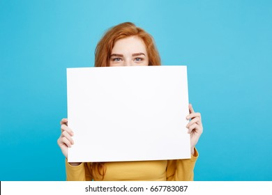 Close up Portrait young beautiful attractive redhair girl smiling showing blank sign. Blue Pastel Background. Copy space.