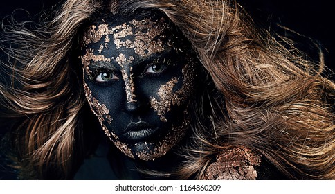 close up portrait of young beautiful blonde girl with black and gold face painting. professional Halloween skull makeup. Gold foil on the black face. Sexy model. flying hair