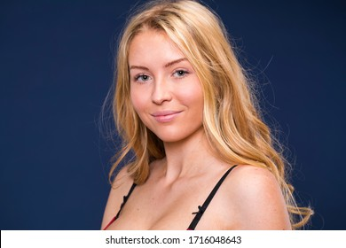 Close up portrait of a young beautiful blonde model, isolated on blue background