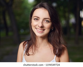 Close up portrait of young beautiful brunette woman with adorable smile enjoying sunlight in city park