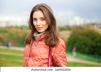 Close up portrait of a young beautiful brunette model in coral coat