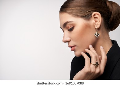 Close up portrait of young beautiful brunette female model presenting golden and silver earrings and ring. Side view of woman in formal suit posing in studio, isolated on white background.