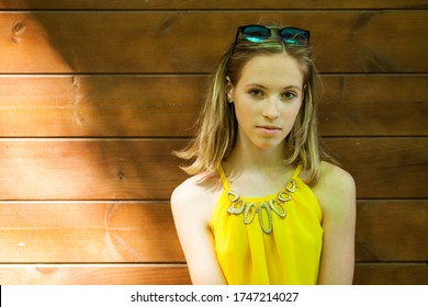 Close up portrait of a young beautiful brunette woman in yellow blouse