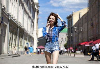 Close up portrait of young beautiful brunette woman in blue jeans short calling by phone and walking in summer street