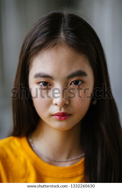 Close up portrait of a young, beautiful, delicate featured elfin Chinese Asian girl model. She is wearing a yellow tee and standing against a grey background of courtroom pillars.