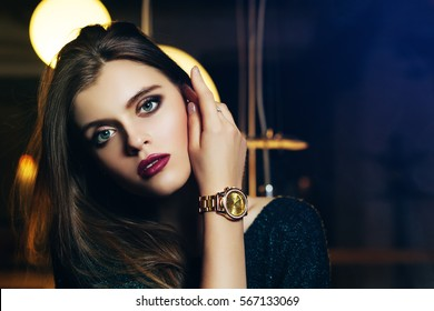 Close up portrait of a young beautiful fashionable woman touching her face. Model looking at camera. Girl with golden watch. Female fashion, beauty concept. Copy, empty space for text