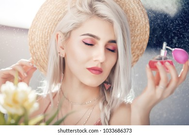 Close up portrait of young beautiful girl holding, using perfume in pink bottle. Model wearing straw hat, posing near spring flowers, against the window. Natural sunny day light.