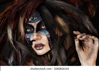 close up portrait of young beautiful girl with Halloween makeup. feathers on the head. third Eye