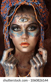 close up portrait of young beautiful girl with glitter on face. professional ethnic makeup. beads crown. third Eye