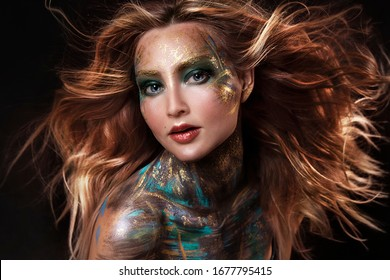 close up  portrait of young beautiful girl with colorful face painting. professional makeup. hair in paint. beauty portrait. orange flying hair