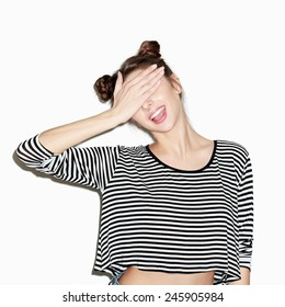 Close up portrait of young beautiful girl having fun and hiding her face with hand. Natural makeup and top knot hairdo. White background, not isolated. Inside.
